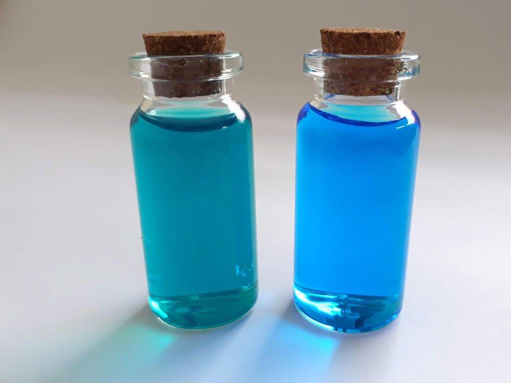 A comparison of the dark green color of an impure copper sulfate solution vs the blue color of a pure one.